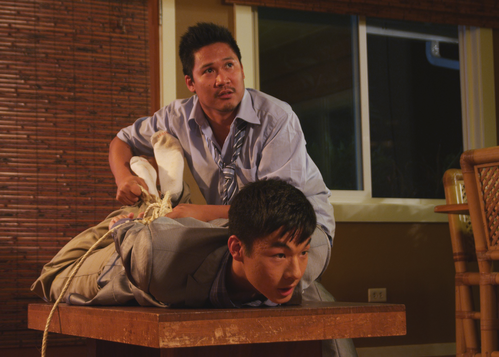 Dante Basco, an Asian American man, looks up while tying up Kevin Wu aka KevJumba, another Asian American man, by his ankles and hands with rope. He is lying on a coffee table.