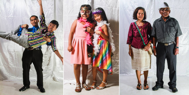 """Three photo booth photos show, from left to right: a young man in a striped shirt and gray pants with arms extended held up by another in a blue shirt and tie; two girls grinning in colorful dresses, silver dress sandals, feather boas, and tiaras; an older couple, the woman on the left with chin-length hair, a fuschia shirt, bone skirt, and sandals, the man on the right in a white hat, striped short-sleeved dress shirt, and grey dress pants."""