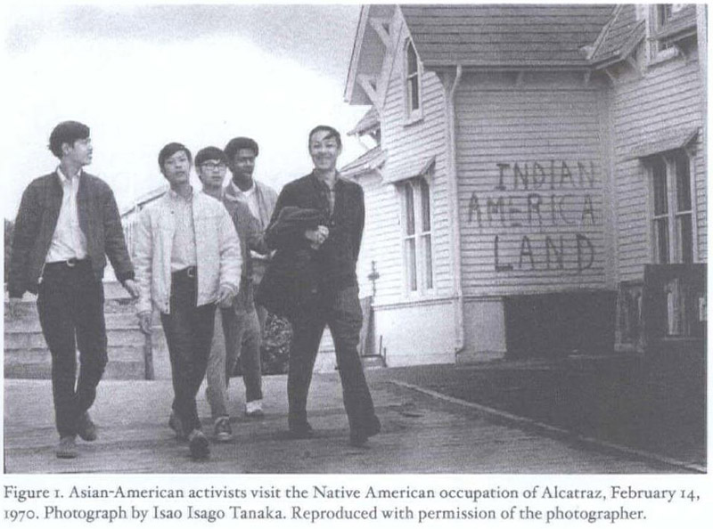 A group of predominantly East Asian men stroll confidently down a street. Graffiti on a house beside them reads 'Indian American Land'. the picture depicts an Asian American delegation to the occupation of Alcatraz in 1970.