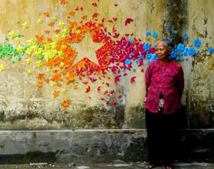 An older Asian American woman in a magenta shirt and black pants stands in front of a concrete wall painted with what looks like a rainbow explosion of stars, creating a star out of negative space in the center.