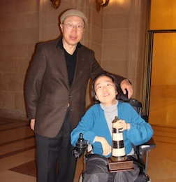 An older Chinese American man in glasses, a brown blazer, and a hat stands beside his daughter, a wheelchair user wearing a blue jacket and a white sweater.