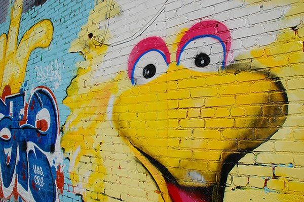 The iconic Sesame Street character Big Bird's face painted, mural-style, on a brick wall.