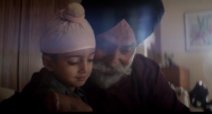 An elderly Sikh man and child are pictured holding one another closely, gazing at something off camera.