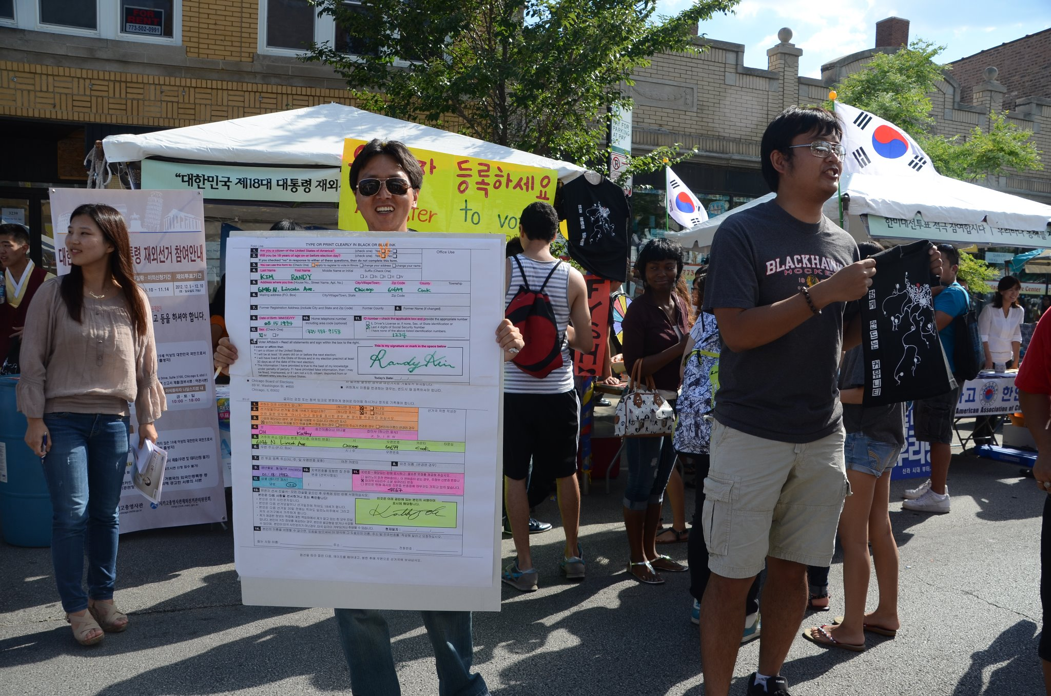Randy Kim holds a blown-up voter registration form, surrounded by people doing voter outreach for KRCC with signs in English and Korean.