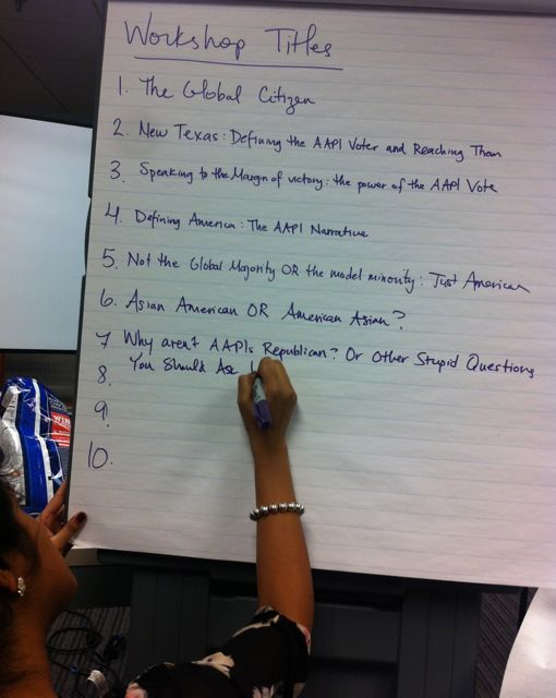 A brown-skinned person writes on a pad of poster paper 'Workshop Titles.' Some of the entries on the list read: 'The Global Citizen,' 'Asian American OR American Asian,' and 'Defining American: The AAPI Narrative.'