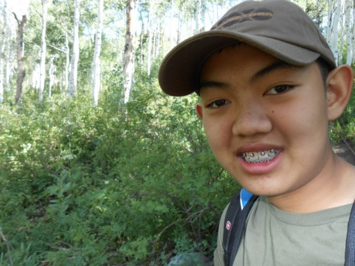 """A 14 year old Asian boy, David Phan, smiles into the camera. He has braces and wears a grey cap. He is outdoors with trees in the background."""