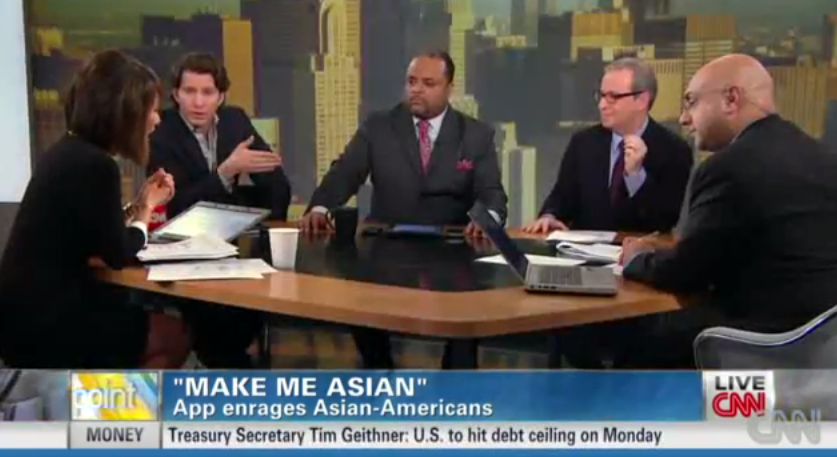 A CNN panel consisting of one black man, three white men, and one Asian woman discussing the asian maker app. The men listen and look at the Asian woman as she speaks.