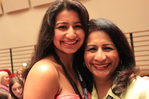 A mother and daughter hug and smile at the camera. The daughter wears a coral tank top. The mother wears a light yellow collared shirt. They both wear conference lanyards.