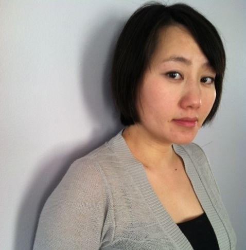 A young Asian American woman with a shoulder-length haircut gazes seriously and sadly at the camera.