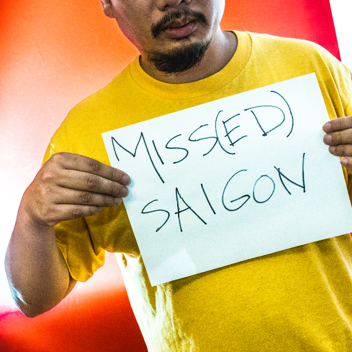 A photo of an Asian man with a mustache and goatee, in a yellow t-shirt, holding a sign that reads 'MISS(ED) SAIGON' against a red background. His eyes are cut off in the image.