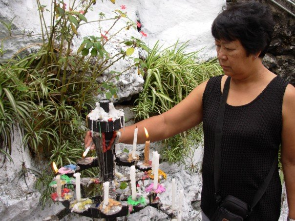 A Filipina woman in a black tank top lights candles on an altar in front of lush vegetation.