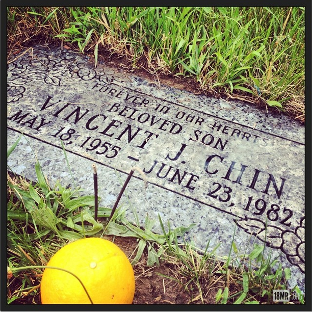 A grave reading 'Forever in our hearts beloved son Vincent J. Chin May 18, 1955 - June 23, 1982.' In front of it is an offering of incense and oranges.