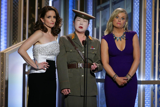 Tina Fey, in a sleeveless white top and black skirt, and Amy Poehler, in a purple dress and blue necklace, grimace awkwardly as they stand on either side of Margaret Cho, dressed in a faux North Korean military uniform, wearing white pancake face makeup, leering into a microphone.