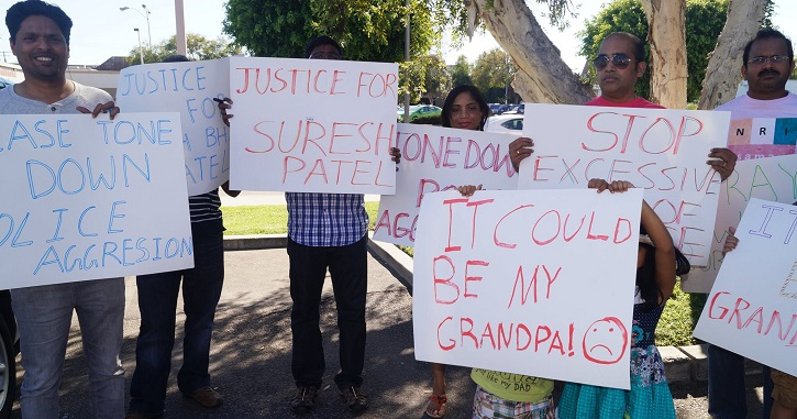 A group of South Asian American protestors outside, smiling, holding signs with messages like 'Tone down police aggression' and It could be my grandpa! (sad smiley face)'