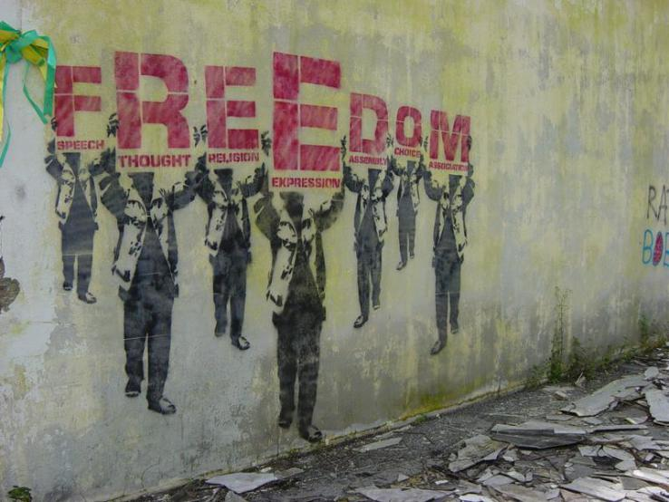 A graffiti stencil on a building wall depicts seven shadowed figures holding protest signs that together read: 'FREEDOM: speech, thought, religion, expression, assembly, choice, association.'