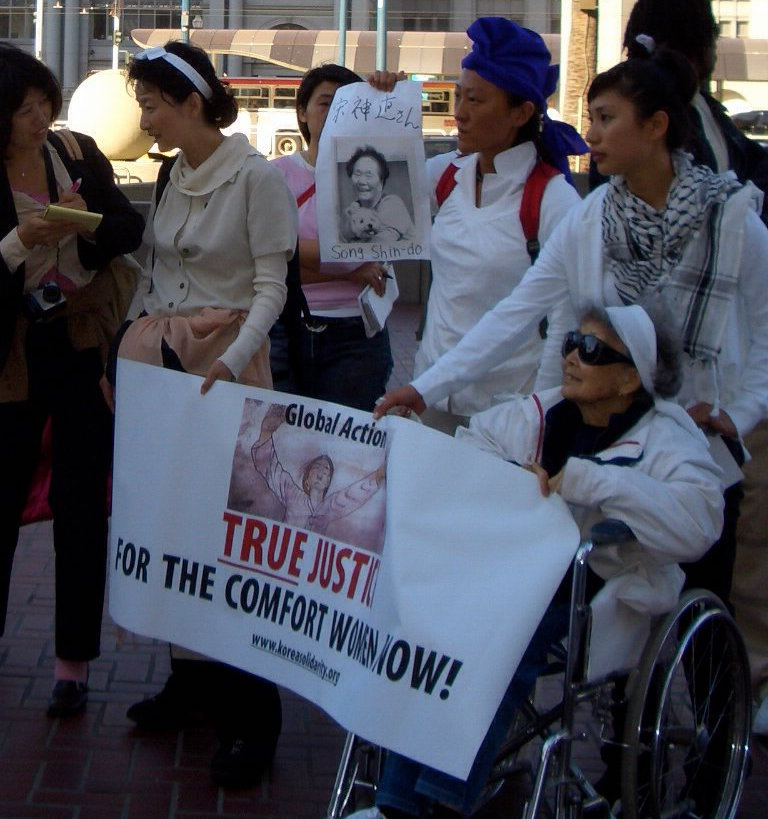 "The author (center) holds an image of Zainichi Korean ""Comfort Woman"" survivor Song Shing-do halmoni, with Yuri Kochiyama (bottom right) at a 2005 protest in front of the Japanese Consulate in San Francisco. Also pictured: renowned Zainichi human rights activist Shin Sugok and Zainichi scholar of Ethnic Studies Kyunghee Ha."