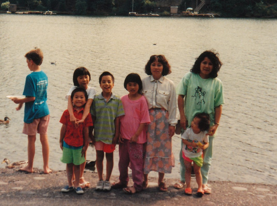 Southeast Asian family with five kids and two women stands in front of beach. Most smile into the camera, others aren't ready.