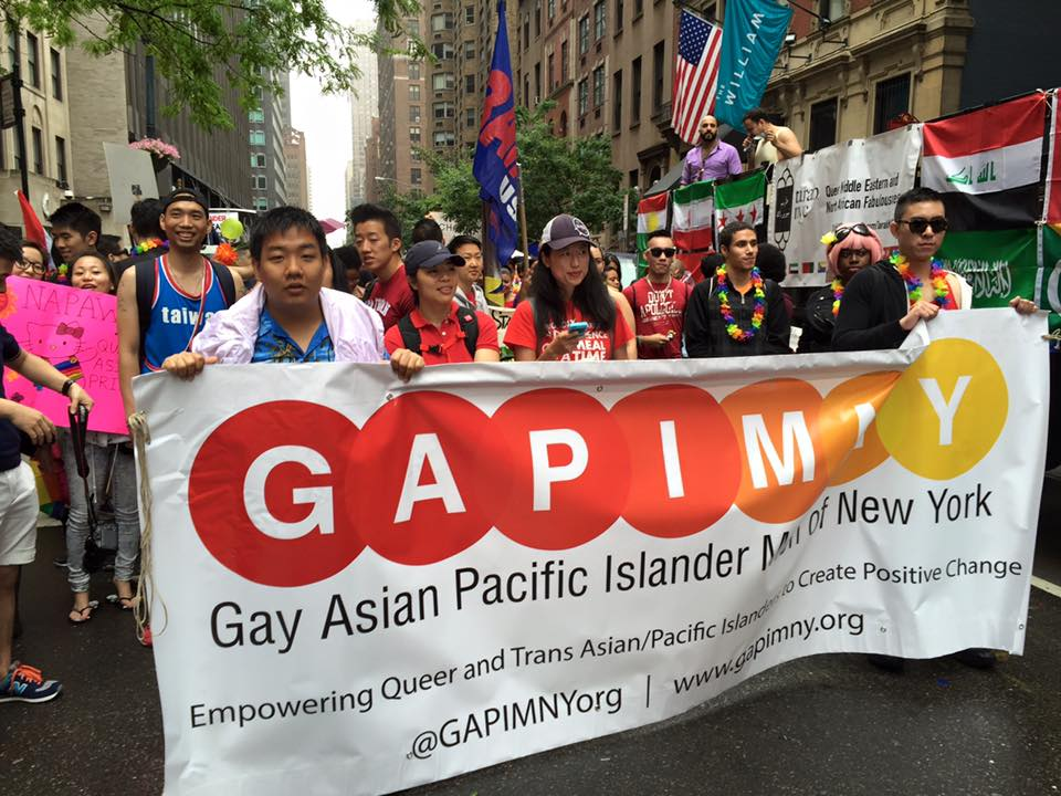 Members of Gay Asian Pacific Islander Men in New York (GAPIMNY) march at the NYC Trans Day of Action in 2014, holding a colorful banner that spells 'GAPIMNY'.