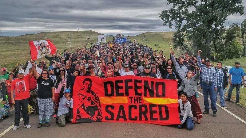 A paved road is filled with countless rows of Native American activists, many with raised fists. A red banner in the front reads: 'Defend The Sacred'. A clear landscape fades into a dark, overcast, sky.